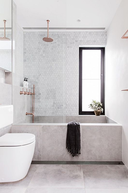 a serene Scandinavian bathroom with mother of pearl and marble tiles, rose gold fixtures and built-in niches