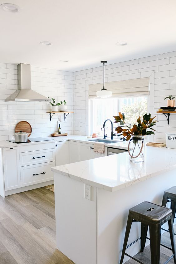 a serene U-shaped white kitchen with white subway tiles and black fixtures plus metal stools is a chic space