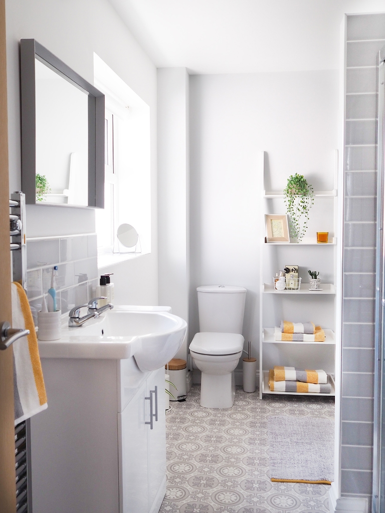 a serene neutral bathroom accessorized with white furniture, white appliances, some grey and yellow touches and decor