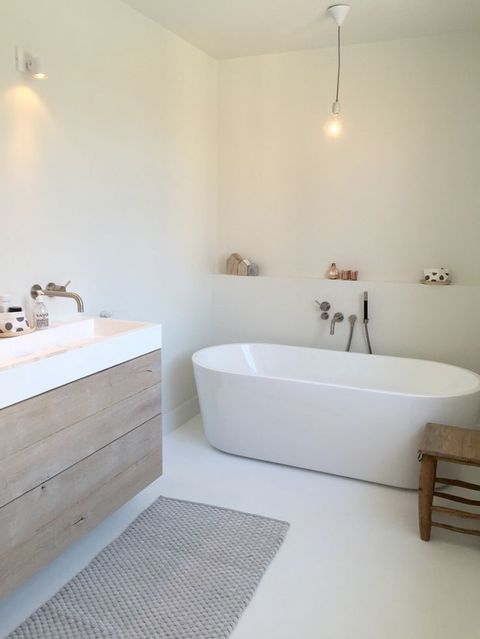 a serene white Nordic bathroom with an oval bathtub, a wooden vanity and a cozy rug is classics of Scandi style