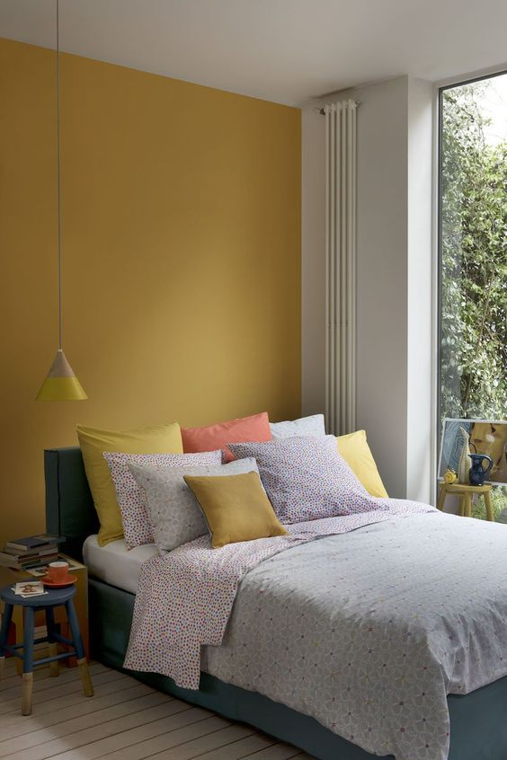 a simple contemporary bedroom with a statement mustard wall, a grey upholstered bed, bright bedding, a color block stool and a pendant lamp
