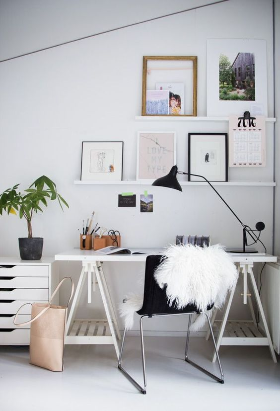 a small Nordic home office with a white trestle desk, a file cabinet, ledges and artworks is a very stylish nook