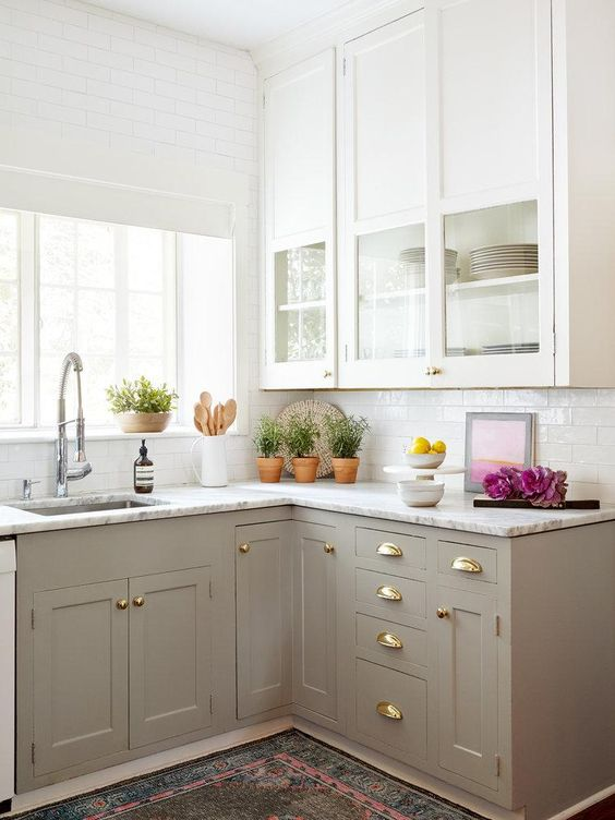 a small and cozy farmhouse kitchen with upper white cabinets and lower grey ones, gold handles and potted greenery
