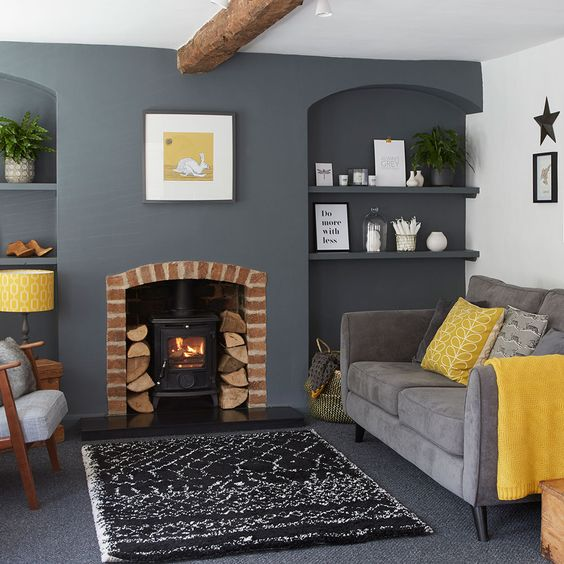 a small and cozy living room with a graphite grey accent wall and floor, a hearth, a grey sofa, mustard touches and a wooden beam