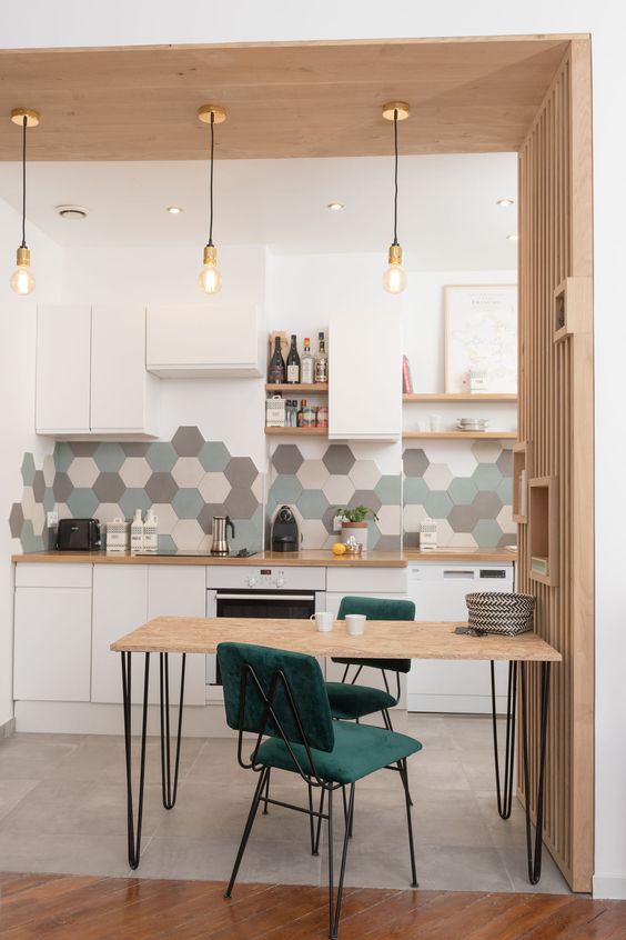 a small and cozy one wall kitchen in white, with wooden countertops, a hex tile backsplash, a mini dining zone with green chairs