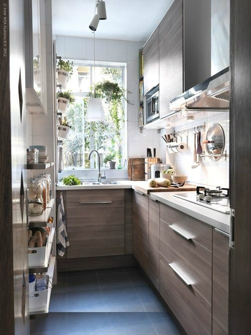 a small and narrow light stained L-shaped kitchen with white countertops, white tiles and some optn shelves