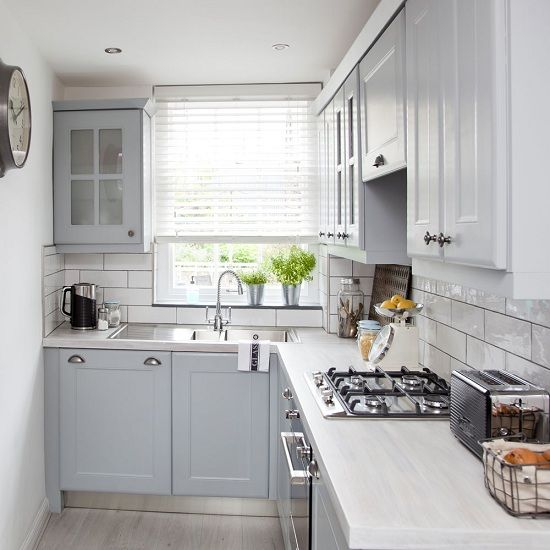 a small dove grey kitchen with neutral countertops, a white subway tile backsplash and a vintage clock is a functional space