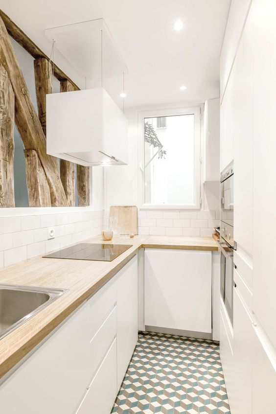 a small white minimalist U-shaped kitchen with butcherblock countertops, white subway tiles and rough wood for deocr