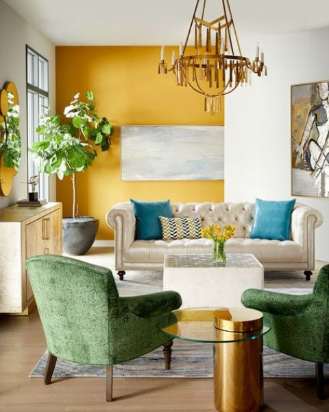 a sophisticated living room with a marigold accent wall, some chic and refined furniture, a gold chandelier and a potted plant