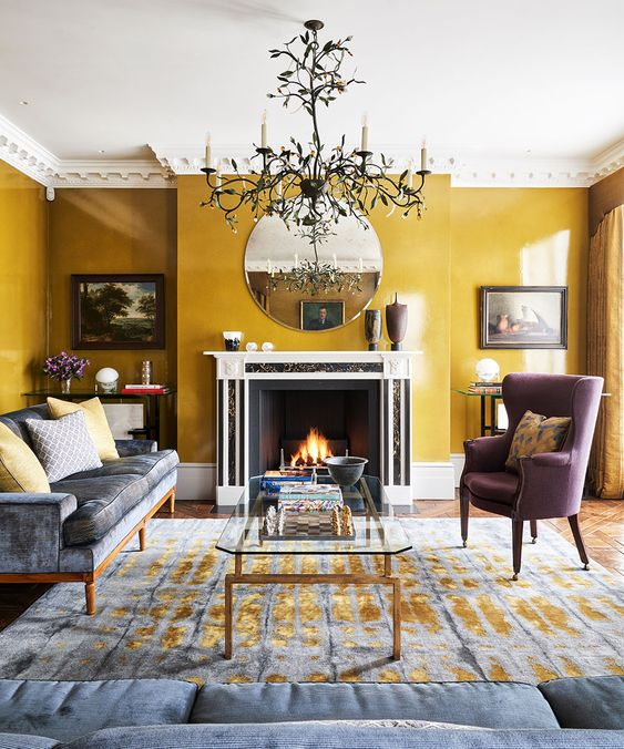 a sophisticated living room with mustard walls, a grey sofa and a mauve chair, a fireplace, a round mirror, a chic chandelier