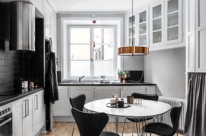 a stylish Scandinavian eat in kitchen in black and white and with a copper pendant lamp looks very cozy