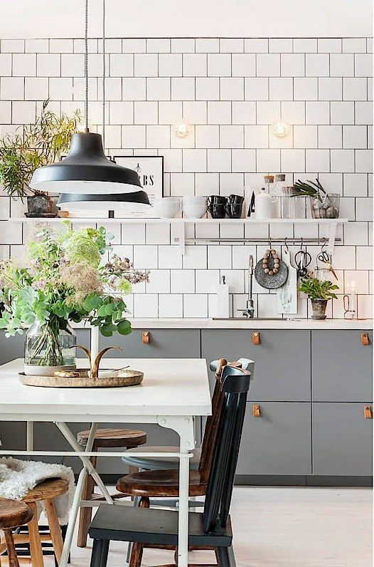 a stylish Scandinavian kitchen with grey cabinets and leather pulls, white square tiles, vintage chairs and pendant lamps
