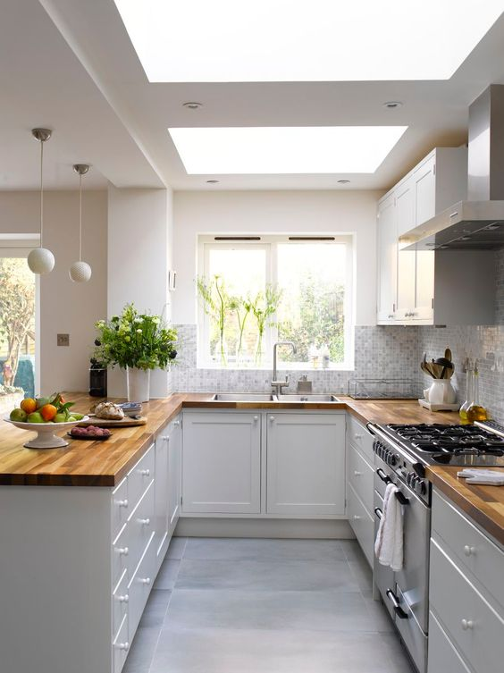 a stylish U-shaped kitchen in white, with only lower cabinets and butcherblock countertops, skylights and pendant sphere lamps