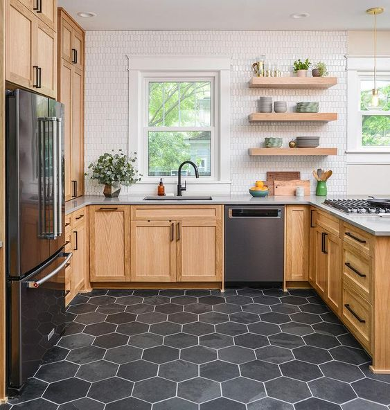 a stylish U-shaped kitchen with wooden cabinets, white narrow tiles, open shelves, grey hex tiles on the floor is all chic