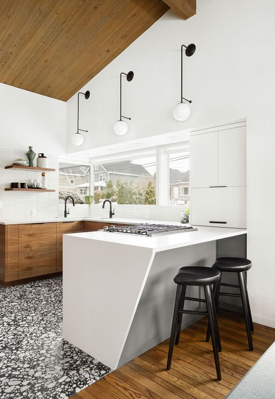 a stylish and catchy U-shaped kitchen with only lower cabinets in white and stained wood, with a terrazzo floor and catchy wall lamps