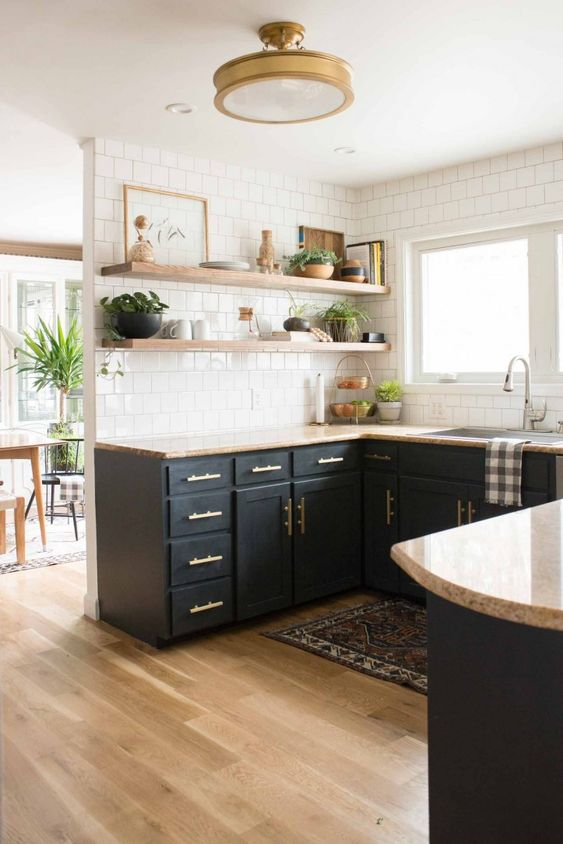 a stylish boho kitchen with black cabinetry, stone countertops, open shelves, white subway tiles, a boho rug and potted plants