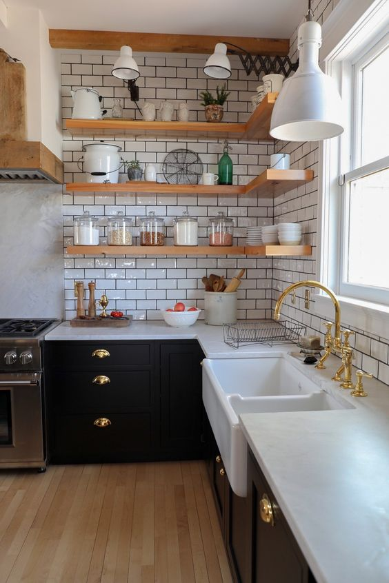 a stylish farmhouse kitchen with black cabinetry, white stone countertops, a white subway tile backsplash and open shelves