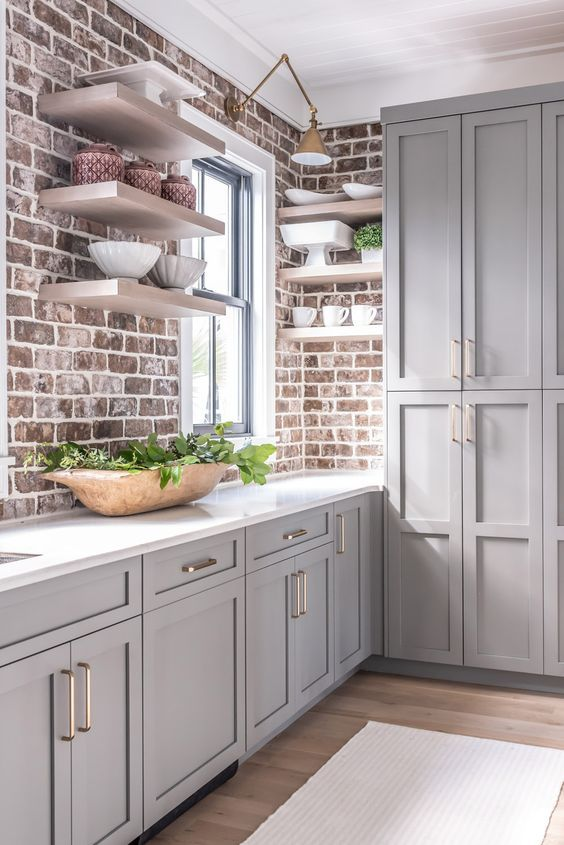 a stylish farmhouse kitchen with grey cabinets, brick walls, open shelves, white stone countertops and a mini pantry on the side