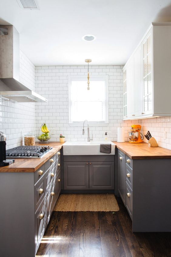 a stylish mid-century modern kitchen with grey lower cabinets and upper white ones, butcherblock countertops and white subway tiles