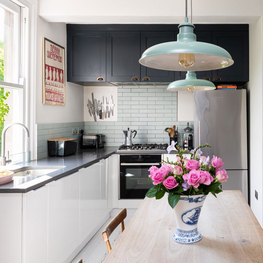 a stylish modern kitchen with black upper cabinets, lower white ones, grey countertops, a blue brick backsplash and a dining space