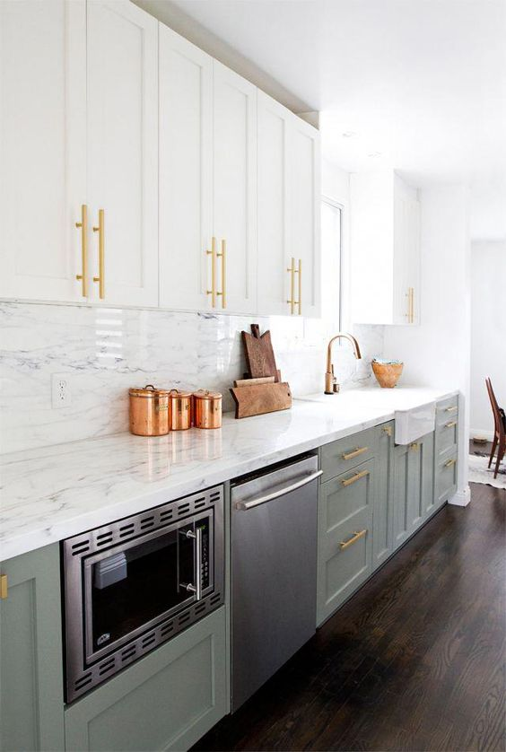 a stylish two-tone one wall kitchen with grey and white cabinets, gold handles and white sotne countertops
