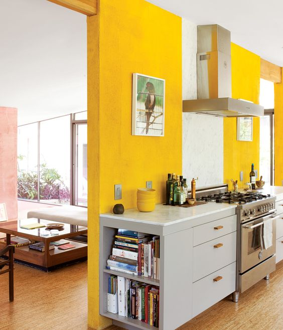 a sunny yellow kitchen with modern grey cabinetry and stainless steel appliances plus bold artworks is veyr statement-like