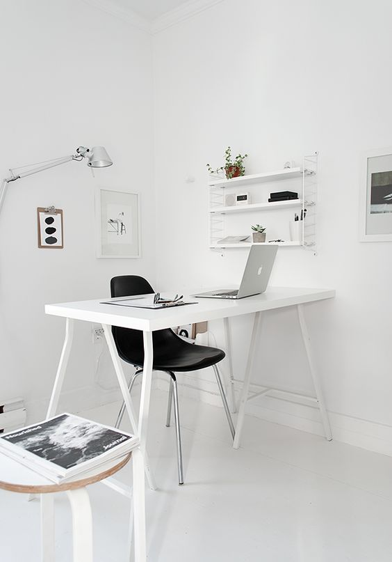 a very minimal Nordic home office with a white desk, a black chair, some stools and a wall-mounted shelf plus lamps