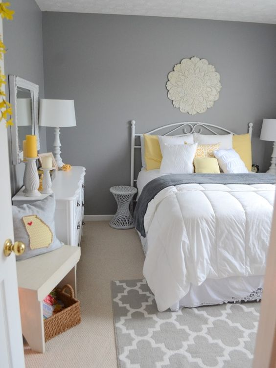 a vintage bedroom with grey walls, white furniture, grey, yellow and white bedding, yellow candles and accessories