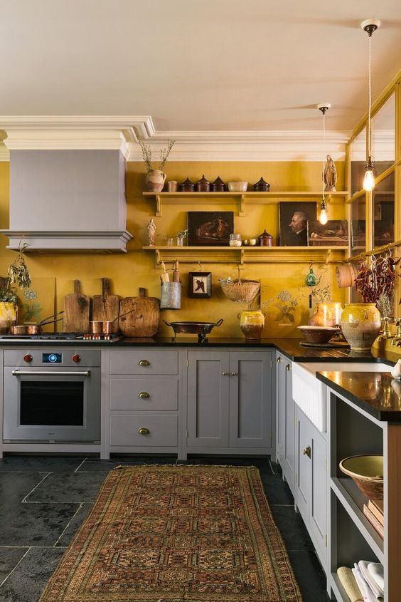 a vintage kitchen with grey cabinets, yellow walls, shelves with artworks and some vintage accessories is very elegant