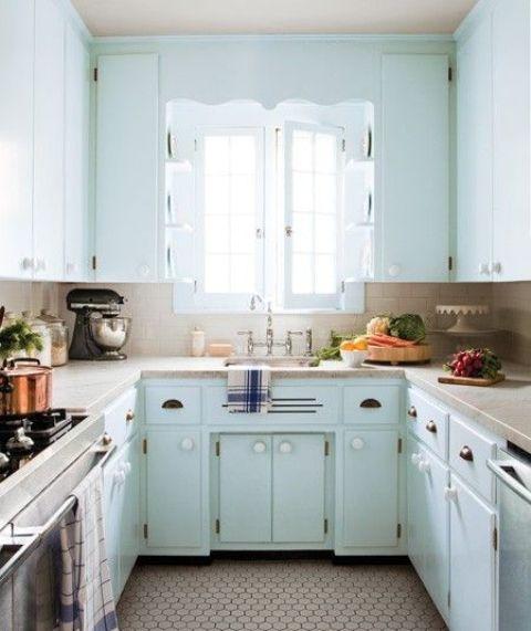a vintage light blue U-shaped kitchen with a hex tile floor, stone countertops and a neutral tile backsplash plus vintage fixtures