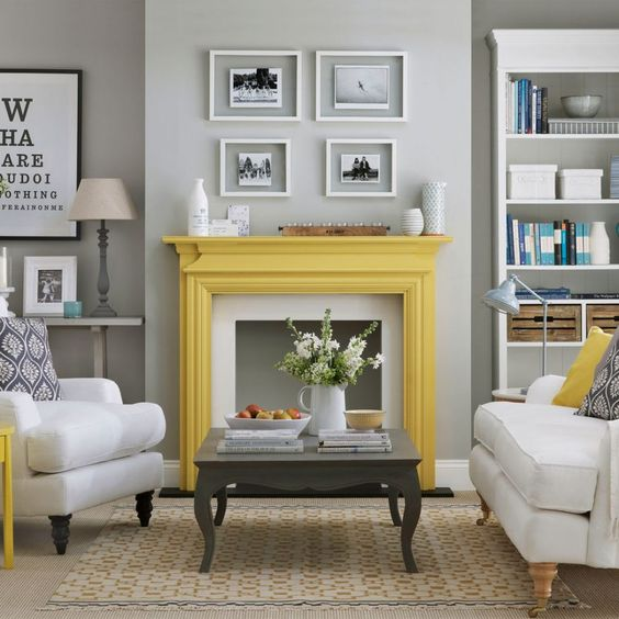 a vintage living room with light grey walls, a bookcase, some artworks, a faux fireplace, neutral furniture, printed textiles