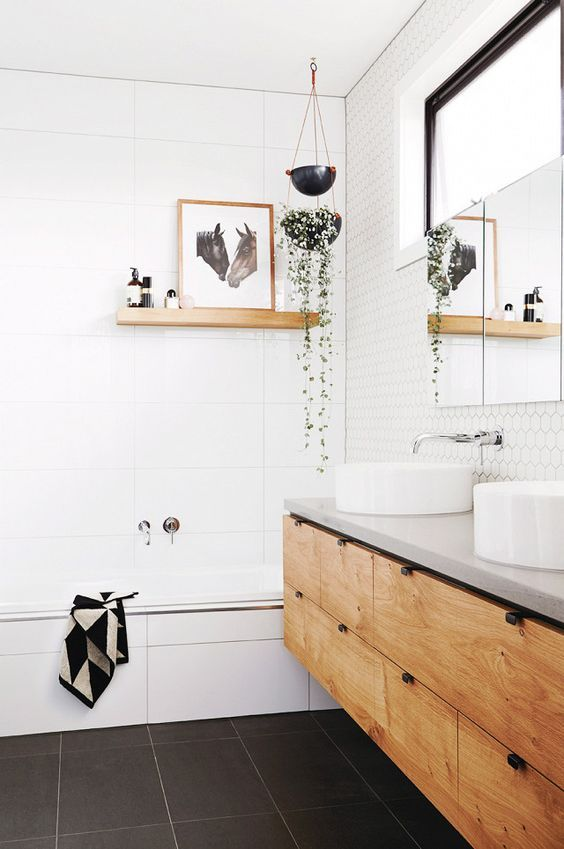 a welcoming Nordic bathroom with white hex and large scale tiles, a double vanity, round sinks and some art and greenery
