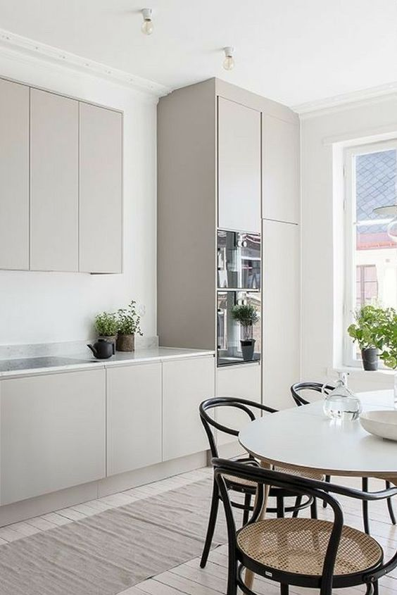 a welcoming Scandinavian kitchen with plain grey cabbinets, a white marble countertop, an oval table and cool retro rattan chairs
