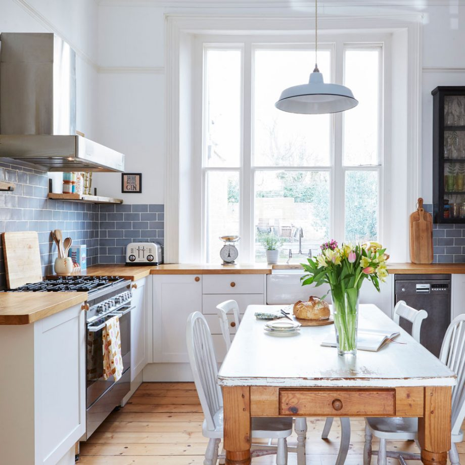 a welcoming and airy L-shaped kitchen with white cabinetry, wooden countertops, a pendant lamp, an eating space and blooms