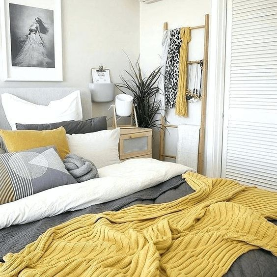 a welcoming bedroom in neutrals, with a grey upholstered bed, grey, yellow and white bedding, some grey and white decor