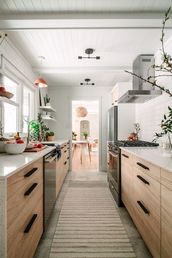 a welcoming light-stained galley kitchen with white countertops and a tile backsplash, with potted greenery and pendant lamps