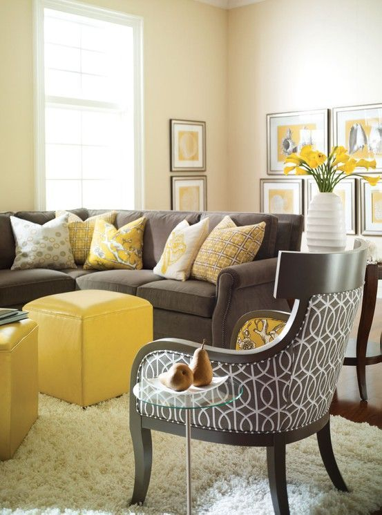 a welcoming living room with buttermilk walls, a grey sofa, a printed chair, yellow ottomans, a bright gallery wall and printed pillows