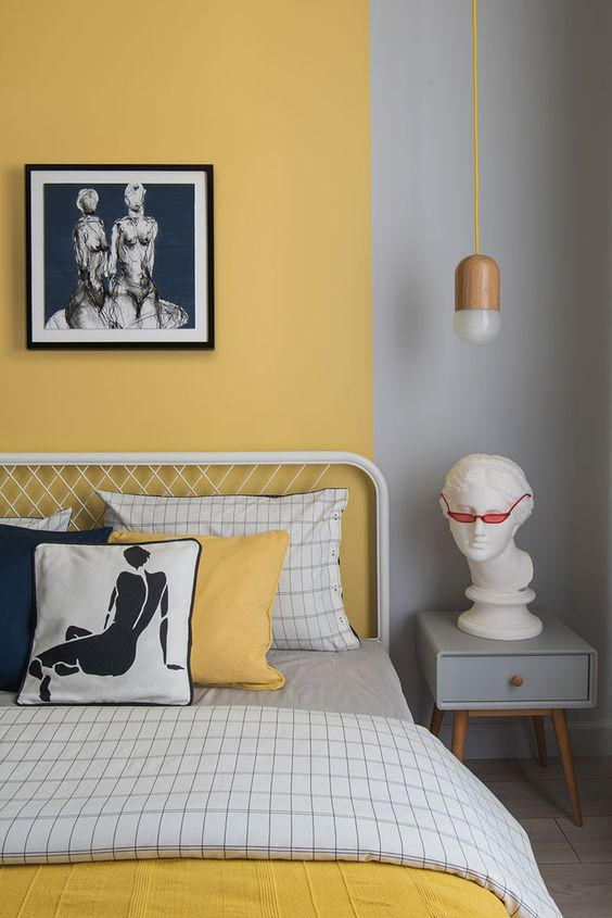 a whimsical bedroom with grey and yellow color block walls, a metal bed, a grey nightstand, some printed bedding and an artwork