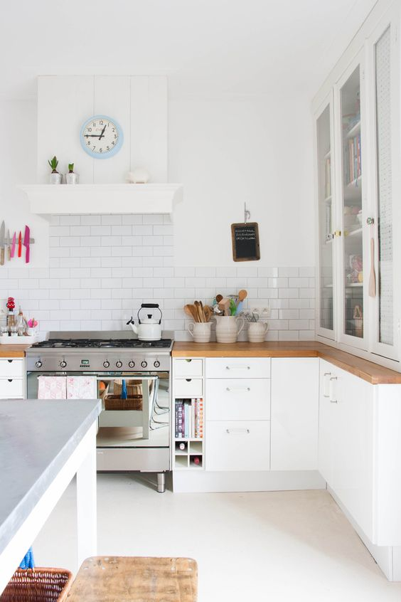 a white Scandinavian kitchen with wooden countertops, a white subway tile backsplash and wooden stools is pretty