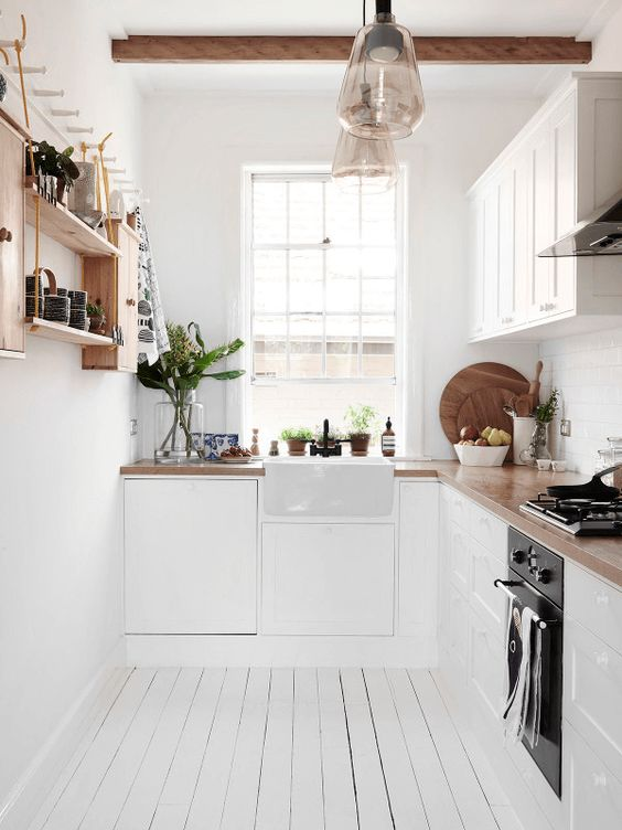 a white Scandinavian kitchen with wooden countertops, an open shelf, wooden beams and pendant lamps is cozy and light-filled
