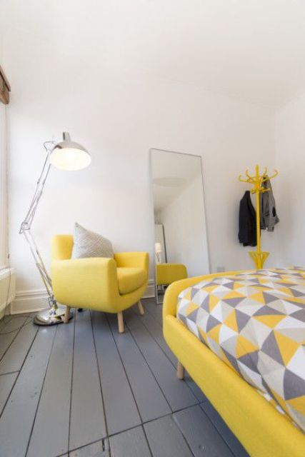 a white bedroom with a grey floor, lemon yellow upholstered furniture, bright grey and yellow bedding and a floor lamp