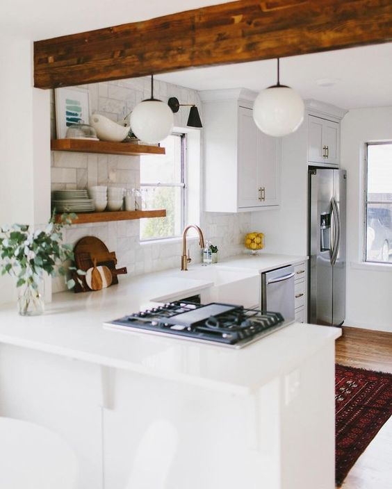 a white farmhouse L-shaped kitchen with chic cabinets, marble tiles, open shelves and a wooden beam, a bright boho rug