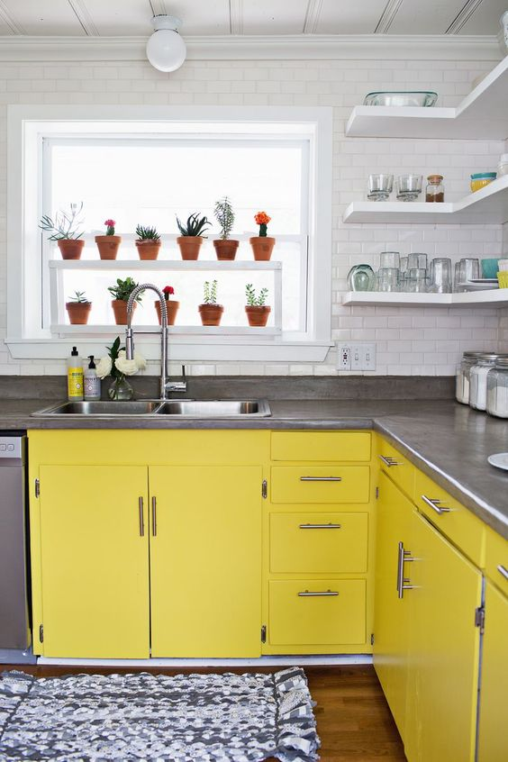 a white kitchen completed with bright yellow cabinets, grey stone countertops and a white subway tile backsplash