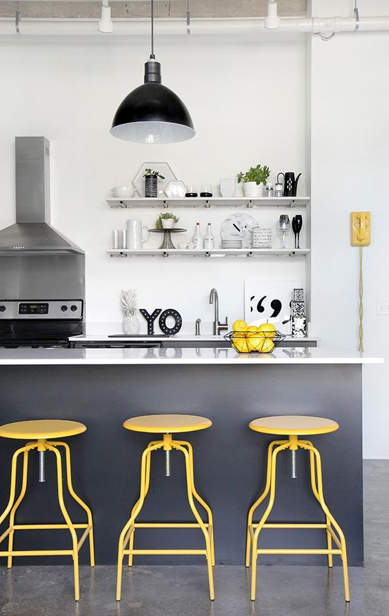 a white kitchen with graphite grey cabinetry, bold yellow stools and other accents is finished with a retro pendant lamp