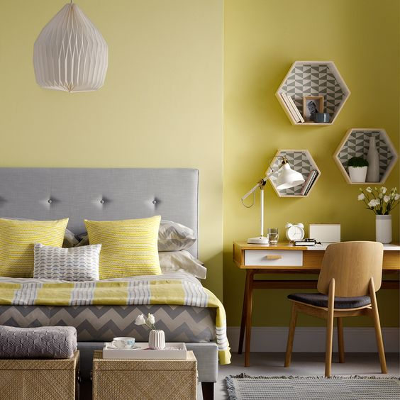 a yellow bedroom with a grey bed, mid-century modern furniture in the corner, woven boxes and bright yellow and grey bedding