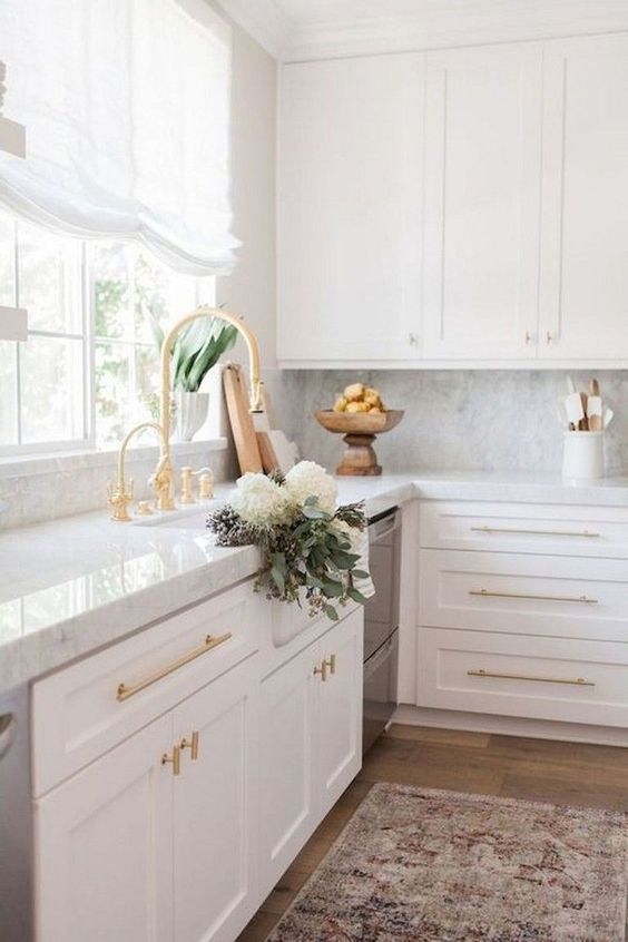 an adorable white modern kitchen with a white marble backsplash, gold fixtures, greenery and a neutral curtain is chic