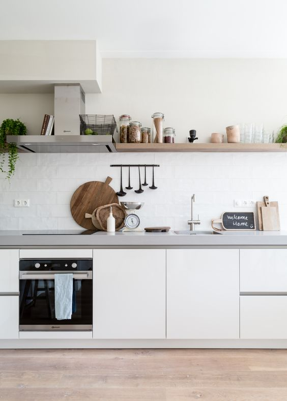 an airy Nordic kitchen with sleek white cabinets, white stone countertops, white tiles and wooden shelves is very cozy
