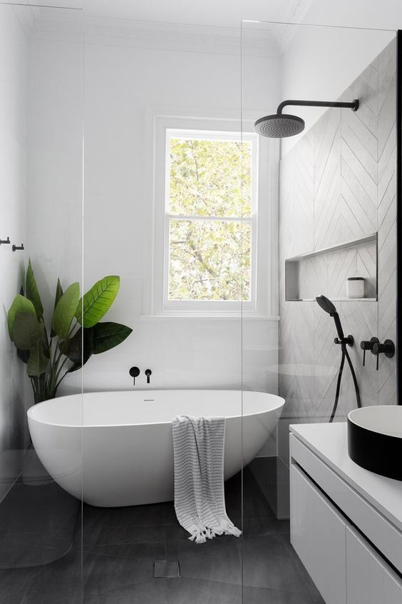 an airy Scandinavian bathroom with grey and white tiles, a floating white vanity, a black sink, a free-standing tub and a statement plant