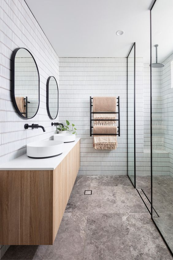an airy Scandinavian bathroom with skinny white and marble tiles, a shower zone, a double vanity and black touches