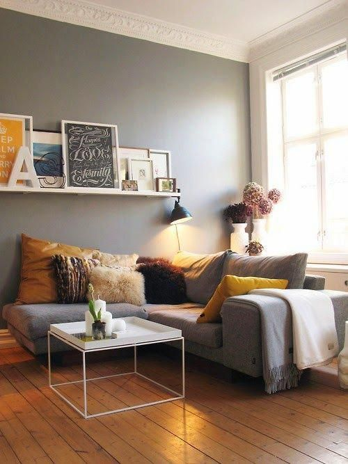 an airy and chic living room with grey walls, a grey sectional, a ledge with artworks, a coffee table and grey and yellow pillows